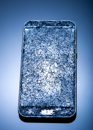 Smarthphone with crushed screen into pieces on a blue reflective surface, studio shot / Destroied equipment