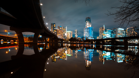 Austin skyline at night and Lamar pedestrial Bridge with bright illuminated buildings reflecting in Lady Bird Lake 免版税图像