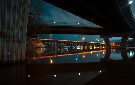 Two Bridges reflecting in a lake at night wirh Bright vibrant reflections and light trails