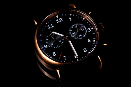 Elegant copper wristwatch with black dial on black background Stock Photo