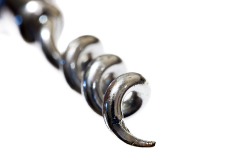 Closeup of the pointed metallic helix of a traditional corkscrew isolated on white background