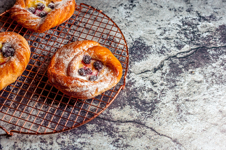 Top view of golden chese danish pasties with blackberries and powder sugar