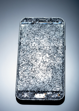 Smarthphone with crushed screen into pieces on a blue reflective surface, studio shot  Destroied equipment Stock Photo