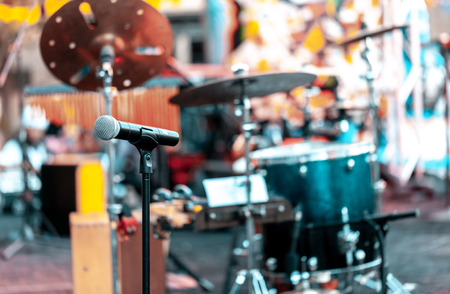 Microphone with drums and other musical instruments on a outdoor stage for performing music. Focus on microphone, blurred background