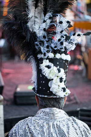 Rear view of man wearing top hat or cylinder hat decorated with feathers durinf a masked festival
