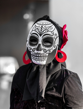 Selective color, black and red, portrait of woman wearing a sugar skull mask for dia de los muertos  day of the dead celebrated in Mexico and soutth border states in the US Stock Photo