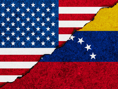 Concept of relationsconflict between Venezueal and the United States of America symbolized flags painted on a  cracked wall Stock Photo