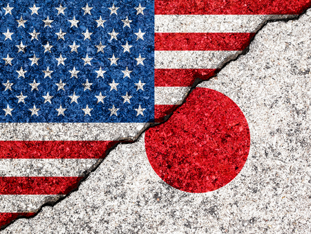 Concept of relations between Japan and the United States of America symbolized flags painted on a cracked wall