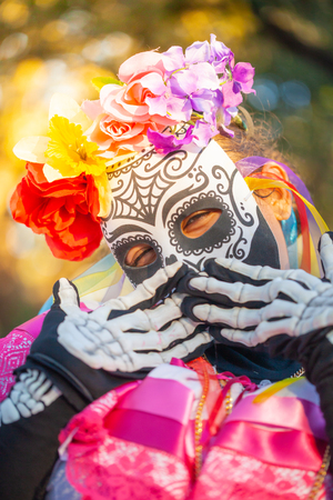 Woman wearing colorful skull mask and paper flowers for Dia de Los MuertosDay of the Dead