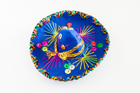 Blue sombrero with colorful ornaments on white background. Symbol of Mexico concept