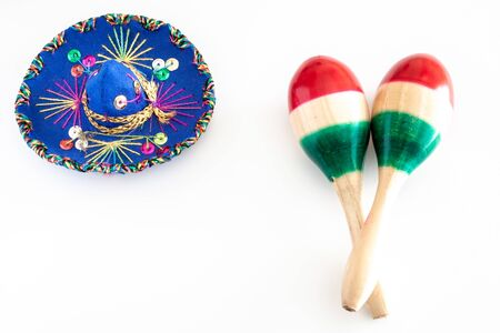 Mexican sombrero and colorful maracas on white background
