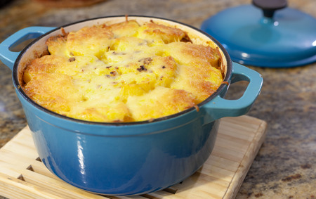 Baked Au Gratin potateos in blue cast iron baking pot with melted cheese on top Фото со стока