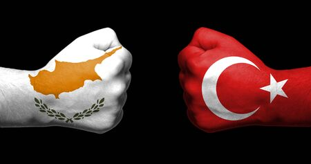 Flags of Turkey and Cyprus painted on two clenched fists facing each other on black backgroundTensed relationship between Turkey and Cypruss concept