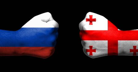 Flags of Russia and Georgia painted on two clenched fists facing each other on black background/Tensed relationship between Russia and Georgia concept Archivio Fotografico