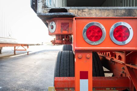 Section of rear part of commercial semi trailer with detail on wheels and signaling lights