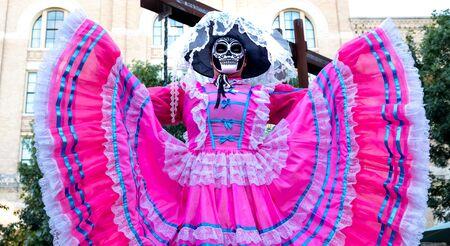 Woman wears sugar skull mask and bright pink Jalisco dress in celebration of Dia de los Muertos / Day of the Dead 版權商用圖片