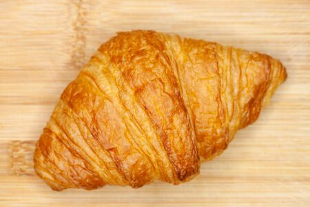 Delicious looking french croisant on a wooden background, top view Фото со стока