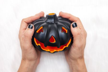 Woman hands with black nail polish holds black carved pumpkin / Haloween concept  background 版權商用圖片