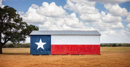 Texas flag painted on old barn. American farmers background, rural scene.