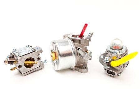 Drie verschillende carburateurs voor tweetaktmotoren geïsoleerd op wit Stockfoto