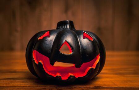Black halowwen pumpkin on wooden background  Haloween background concept with jack-o-lantern Фото со стока