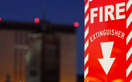 Fire extinguisher sign wirh building in the background, fire danger concept Stock fotó