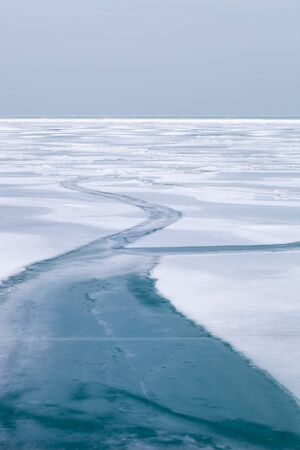 Frozen lake surface covered in snow with a frozen ice path Фото со стока