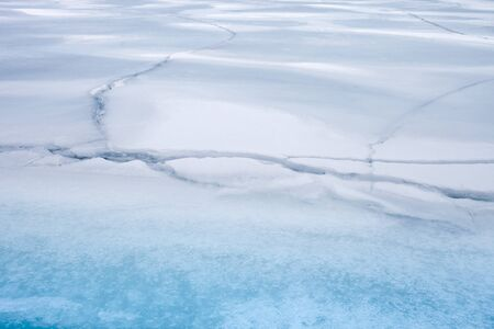 Frozen lake surface covered in snow with multiple surface cracks