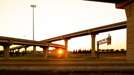 Intersection of elevated highway at sunset with bright sunset shing thru pillars
