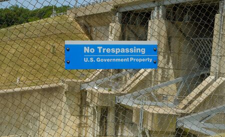 US government no trespassing sign posted om wired fence limiting access to a dam Фото со стока - 131725369