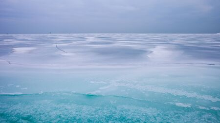 Colorful frozen lake surface during a heavy overcast day