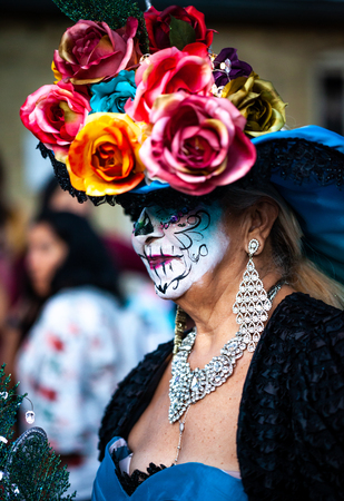 Woman with sugar skull makeup and mexican traditional paper flowers headdress attends dia de los muertos celebration