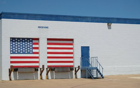 Warehouse with american flag painted receiving docks / Logistics building with entrance door and white and blue brick wall with copy space