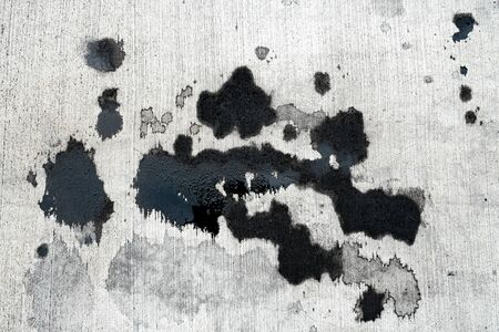 Stains of car oil drips and spots on concrete