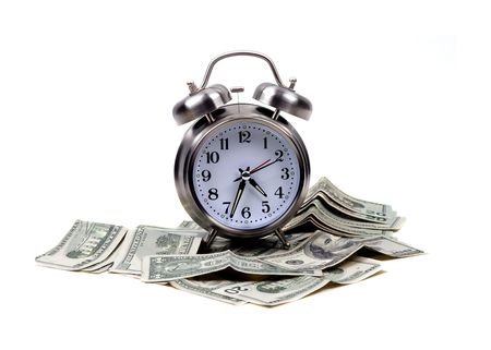 An isolated alarm clock places atop lots of money for the concept of time and money.