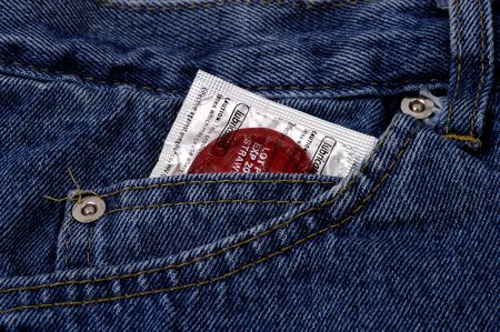 An unused red flavored condom peeking out of a jeans pocket.