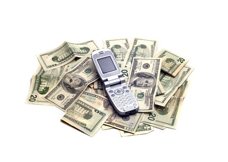 An open cellphone in the midst of lots of American dollars. Foto de archivo