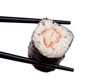 A piece of crab sushi between black chopsticks and isolated against a white background.