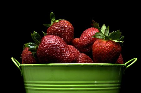 Fresh red strawberries in a green pail against a black background.