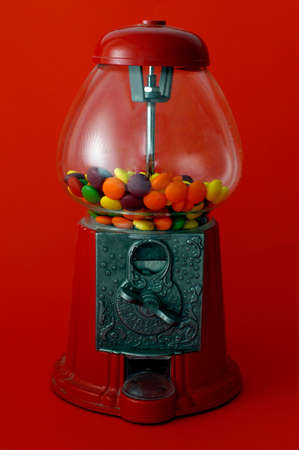 A gumball machine against on a red background. photo