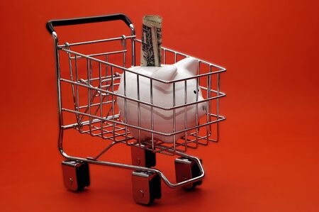 A piggy cart stuffed with money in a shopping cart.