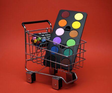 A paint palette and some oil pastels in a shopping cart. Could represent back to school supplies or shopping for an art project. Foto de archivo