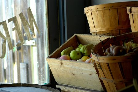 Interior shot of a merchant storefront display of boxes and barrels selling fruit and other produce.
