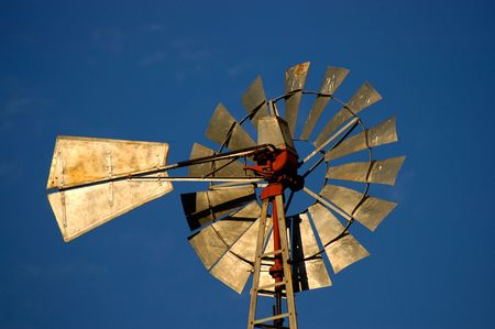 Windmill blades illuminated by the sun against a blue sky.