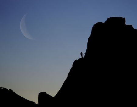 A silhouette of a rock climber on the edge of the cliff. The size difference between climber and cliff is vast. This could represent struggle or overcoming fears. Foto de archivo
