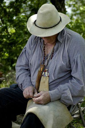 flint: An elderly native american making flint arrowheads by hand. Stock Photo