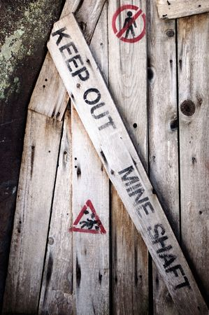A wooden door warning people of the danger of a mine shaft, telling them to keep out. Foto de archivo