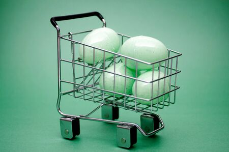 Several green colored easter eggs in a shopping cart. Could represent easter shopping. Foto de archivo