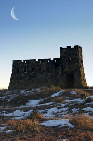 A castle standing on snow-covered prairie under a moonlit evening.