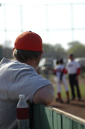 watcher: A father watches his son playing youth baseball. Stock Photo